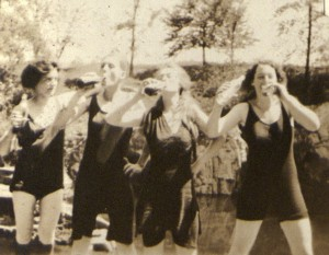 Three young women wearing early-20th century style bathing suits are pictured chugging frombow bottles, while a fourth looks on, bottle in hand and leaning her elbow on the shoulder of the woman next to her.