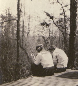 Two Bryn Mawr students in white athletic clothing of the early 20th century sitting on a porch, their backs to the viewer. A forest of fir trees is visible in the middle-distance.